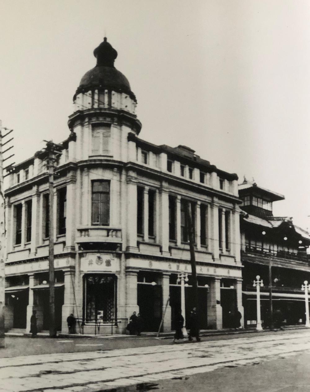 洋館建ての本店と市電の線路